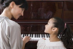 A mother and daughter playing the piano